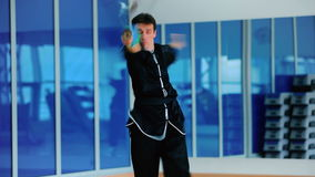 Sportsman in black costume training the wushu with sword in the gym stock footage