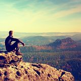 Sportsman in black sit on the peak of sandstone rock in rock empires park watching into Sun. Stock Image