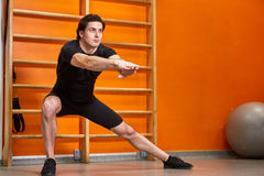 Sportsman in the black sportwear at the gym doing stretching exercises against bright orange wall. Stock Photo
