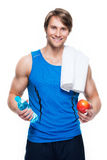 Sportsman in blue shirt holds water and apple. Stock Photo