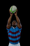 Sportsman catching ball while playing rugby. Against black background stock image