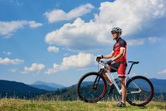 Sportsman cyclist standing with cross country bike, enjoying beautiful view of distant mountains royalty free stock images