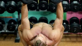 Sportsman doing exercises with dumbbell in the gym. Athletic sportsman doing exercises with dumbbell on bicep muscles and chest in the gym stock video footage
