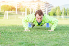 Sportsman doing exercises in a soccer field Stock Images