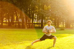 Sportsman doing gymnastic exercise in park. Stock Images