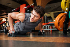Sportsman doing push-up exercises in gym. Handsome young sportsman doing push-up exercises in gym royalty free stock photo