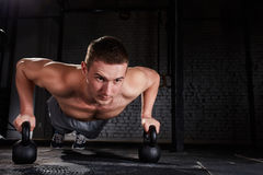 Sportsman doing push-ups exercise with kettlebell in a crossfit workout against brick wall Royalty Free Stock Photo