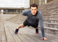 Sportsman doing push-ups on one hand outdoors. Portrait of sportsman in grey tracksuit doing push-up exercises on one hand outdoors in the city Royalty Free Stock Photography