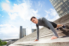 Sportsman doing push-ups outdoors on city stairs Royalty Free Stock Image