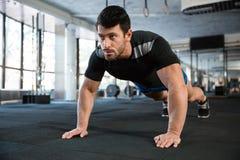 Sportsman doing push-ups. Sportsman wearing blue shorts and black t-shirt doing push-ups stock image