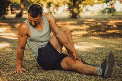 Sportsman doing stretching exercise. Young sportsman doing stretching exercise, preparing for morning training in the park. Fitness, sport, lifestyle concept Royalty Free Stock Photography
