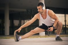 Sportsman doing stretching exercise. Young sportsman doing stretching exercise, preparing training in the park. While exercising, he listens to music via Stock Image