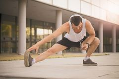 Sportsman doing stretching exercise. Young sportsman doing stretching exercise, preparing training in the park. While exercising, he listens to music via Stock Photos