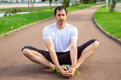 Sportsman doing stretching exercises. Attractive spotrsman doing stretching exercises outdoors in a track Stock Images
