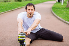 Sportsman doing stretching exercises outdoors. Attractive mid adult spotrsman doing stretching exercises outdoors in a track Stock Images