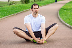 Sportsman doing stretching exercises outdoors. Attractive spotrsman doing stretching exercises outdoors in a track Stock Photos