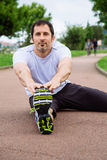 Sportsman doing stretching exercises outdoors. Attractive spotrsman doing stretching exercises outdoors in a track Royalty Free Stock Photography
