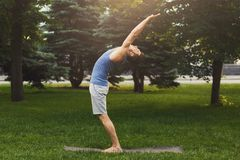 Sportsman doing stretching exercises outdoors. Side view. Young man leaning back in park, copy space Stock Photography