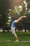 Sportsman doing stretching exercises outdoors. Side view. Young man leaning back in park, copy space Royalty Free Stock Image
