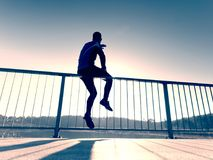 Sportsman doing stretching at handrail in park. Silhouette against sun, Stock Photo