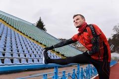Sportsman doing stretching on stadium stock image