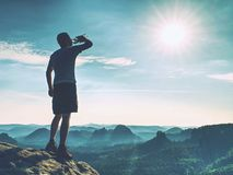Sportsman drinking water in nature. Sweaty tired man. Drink water after jogging in outdoor royalty free stock photo