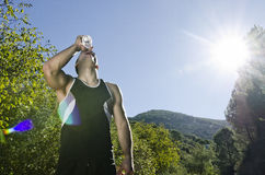 Sportsman drinking water with sunflare Royalty Free Stock Photography