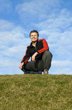 Sportsman with dumbells. A handsome smiling forties man wearing a tracksuit is sitting on the grass with his dumbells Stock Photo