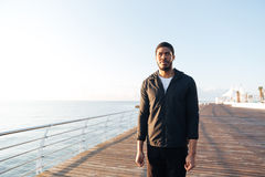 Sportsman with earphones standing on pier and listening to music Stock Photography