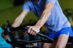 Sportsman engaged on stationary bike Stock Image