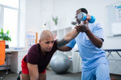 Sportsman feeling ache exercising with barbells after injury. Some ache. Young bald sportsman feeling some ache exercising with barbells after injury stock image