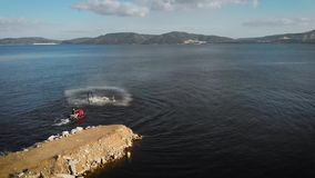 Sportsman is flying on flyboard on lake in daytime, performing trick, aerial moving around view. Male acrobat is flying on flyboard on sea in summer day stock video