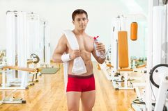 Sportsman in gim holding bottle of water Royalty Free Stock Photo