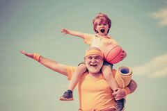 Sportsman grandfather and healthy kid with basketball ball on blue sky background. Sport for little children. Different
