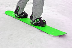 Sportsman with green snowboard on white snow, seasonal sport, Stock Image