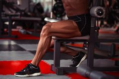 Sportsman in gym. Guy doing exercises. Closeup portrait of legs with veins. Male model with tanned skin. Sexy man Stock Images