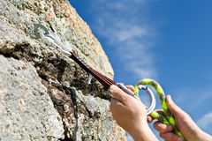 The sportsman hangs up carbine in rock. Two hands of climber fix equipmant on rock Stock Photography