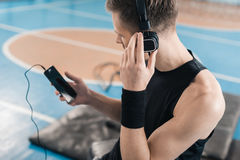 Sportsman in headphones using smartphone in sports center Royalty Free Stock Photography