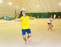 Sportsman hits ball by racket on beach tennis game. On covered court Royalty Free Stock Images