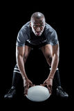 Sportsman holding ball while playing rugby. Over black background stock photo