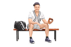 Sportsman holding a baseball seated on bench Royalty Free Stock Photography