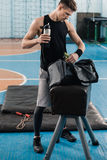 Sportsman holding bottle and looking in bag after exercising in gym Stock Photography