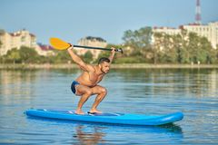 Sportsman holding long oar over head, swimming on paddle board in city lake. Portrait of sportsman holding long oar over head, swimming on paddle board in city stock image
