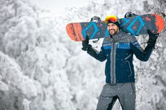 Sportsman holding ski board and return from skiing terrain. Sportsman holding ski board and return from terrain royalty free stock photos
