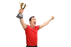 Sportsman holding a trophy and celebrating. Studio shot of a young sportsman holding a trophy and celebrating victory isolated on white background royalty free stock photos