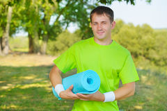 A sportsman holding yoga mat Royalty Free Stock Images