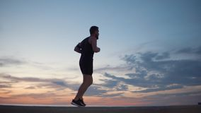 Adult male jogger is running against cloudy sky in sunset time stock video footage