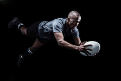 Sportsman jumping for catching rugby ball Stock Photos