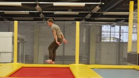 Male acrobat is bouncing through few of trampolines in a gym stock footage