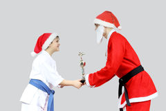 Sportsman in karategi receives from Santa Claus with a black belt karate Cup Stock Photos